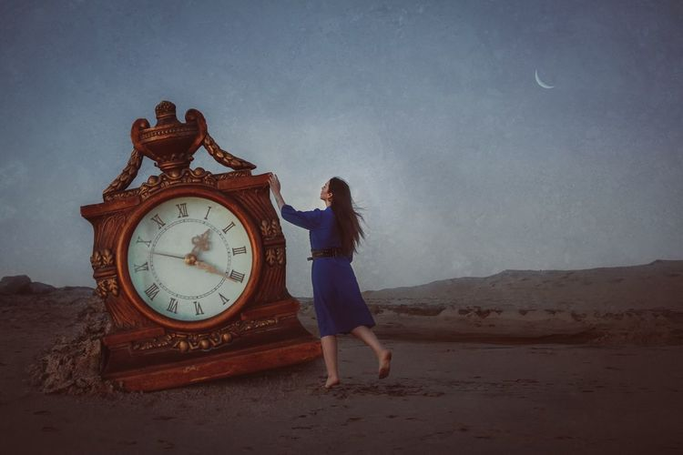 Full length of woman touching clock on sand at beach against sky