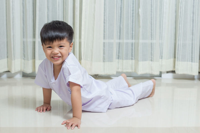 Portrait Of Boy Cheerful Boy Lying Against Curtain At Home