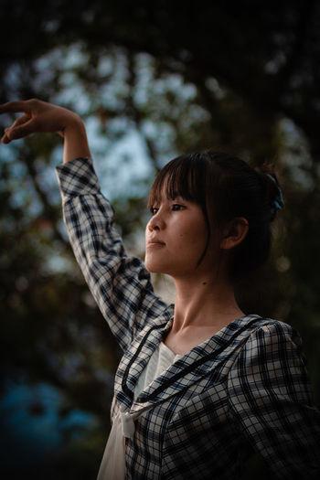 Portrait of girl standing against tree