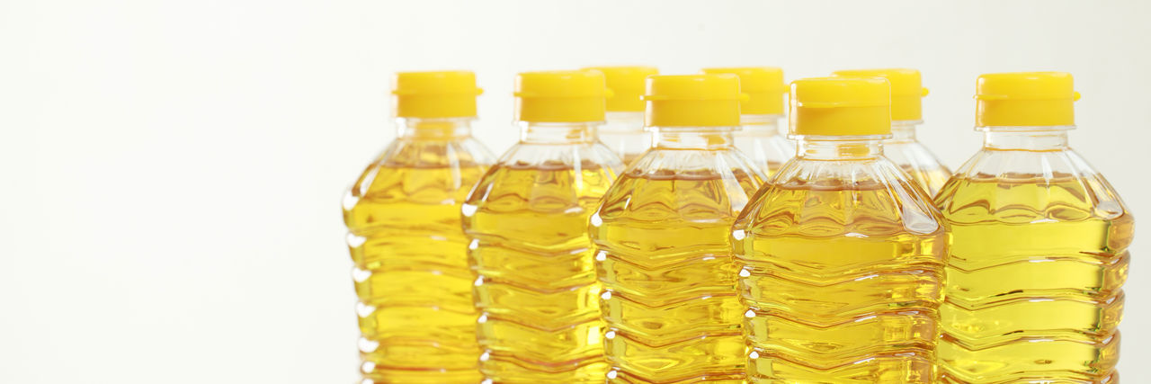 Close-up of yellow bottles against white background