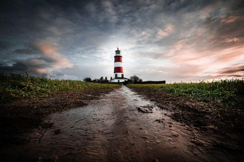 Road leading towards lighthouse amidst field against sky