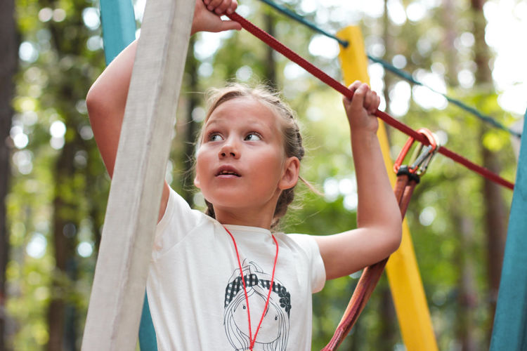 Cute girl 8 years old in adventure rope town, selective focus Arms Raised Child Childhood Day Focus On Foreground Front View Girl Girls Headshot Holding Human Arm Innocence Leisure Activity Lifestyles Offspring One Person Outdoors Playing Portrait Rope Tree