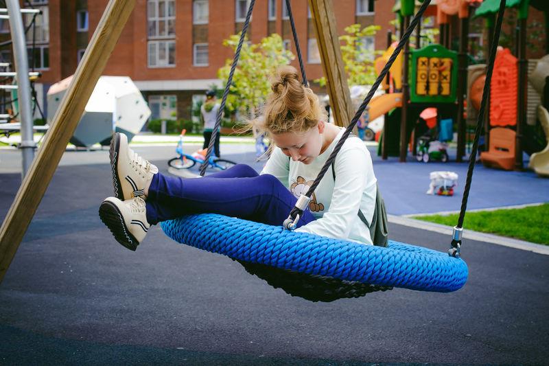 Full length of teenage girl sitting on swing at playground