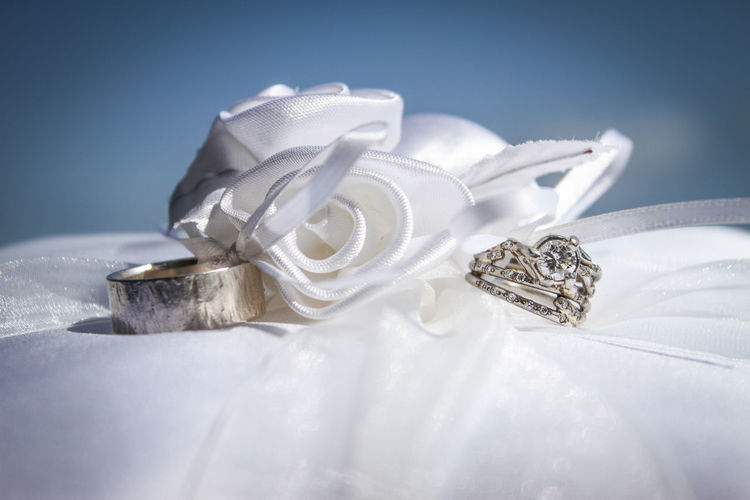 Close-up of wedding rings by artificial rose on pillow