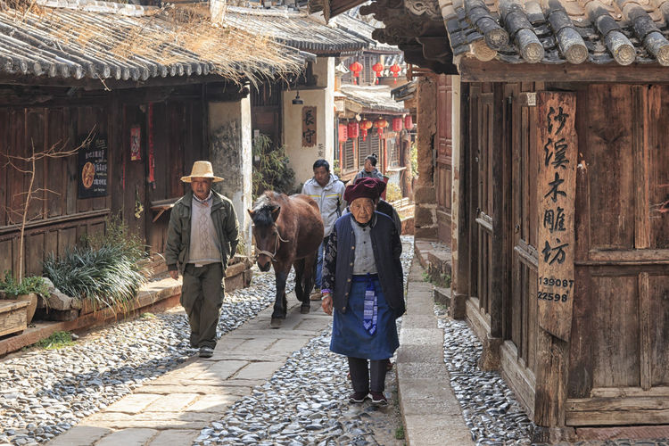 Shaxi, China - February 22, 2019: Horses riding in the center of Shaxi old town at dusk Shaxi Yunnan China Horses Horse South Silk Road Tea Horse Road Old Town Ancient History ASIA