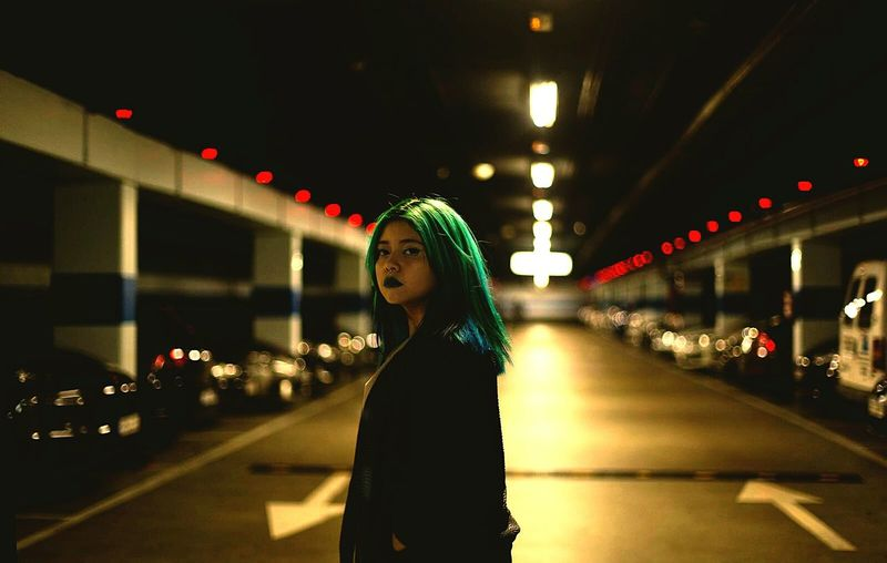 Portrait Of Woman With Dyed Hair Standing In Illuminated Basement