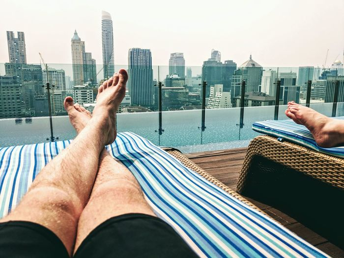 Low angle view of man relaxing at poolside against modern buildings