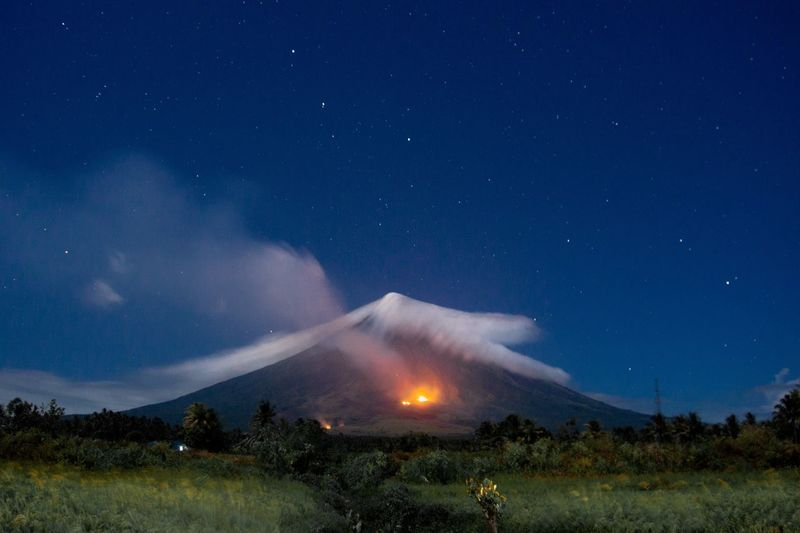 Scenic view of mayon volcano with bush fire at night