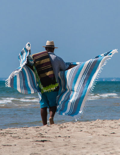 Rear View Of Man With Sheet Walking At Beach Against Sky