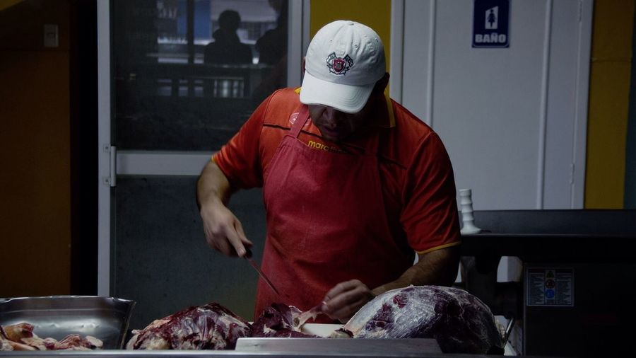 Close-Up Of Butcher Cutting Meat In Butcher Shop