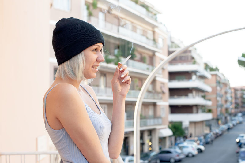 Side View Of Woman Smoking Cigarette In Front Of Urban Scene