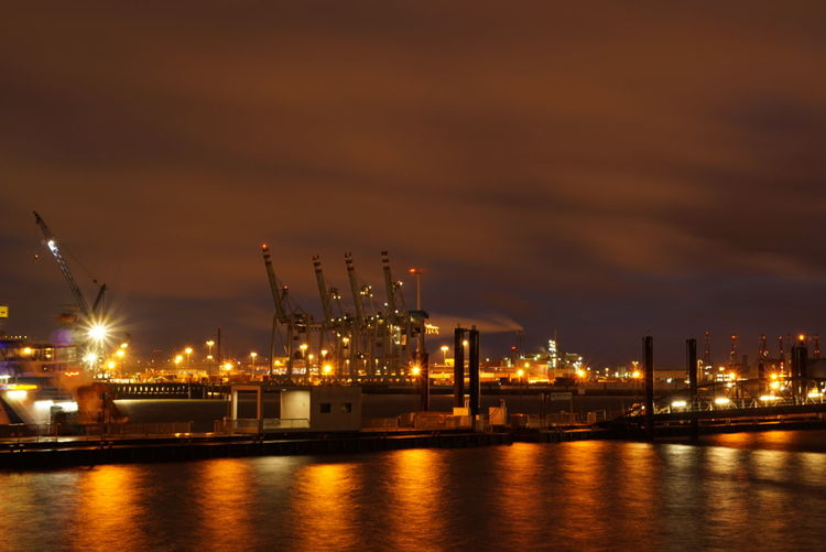 View of cranes at commercial dock at sunset