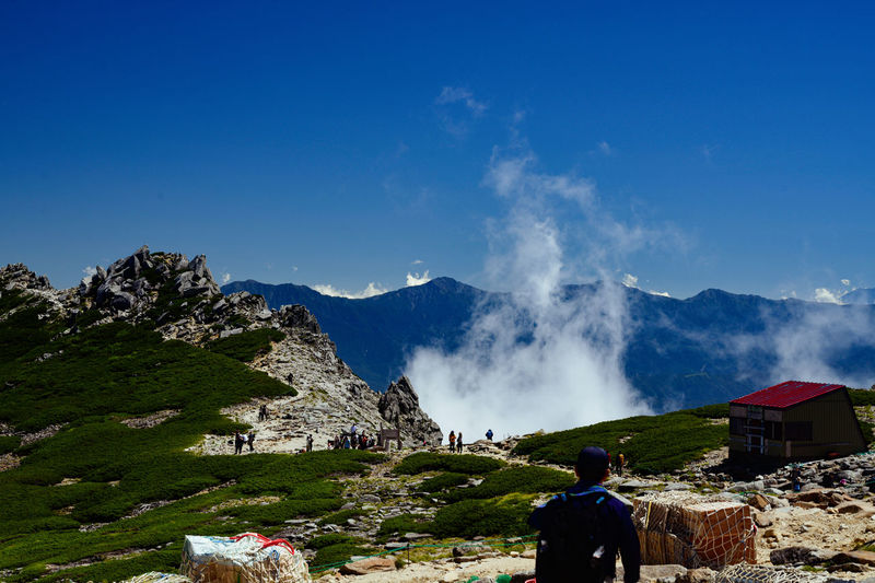 Rear view of people on mountain against blue sky