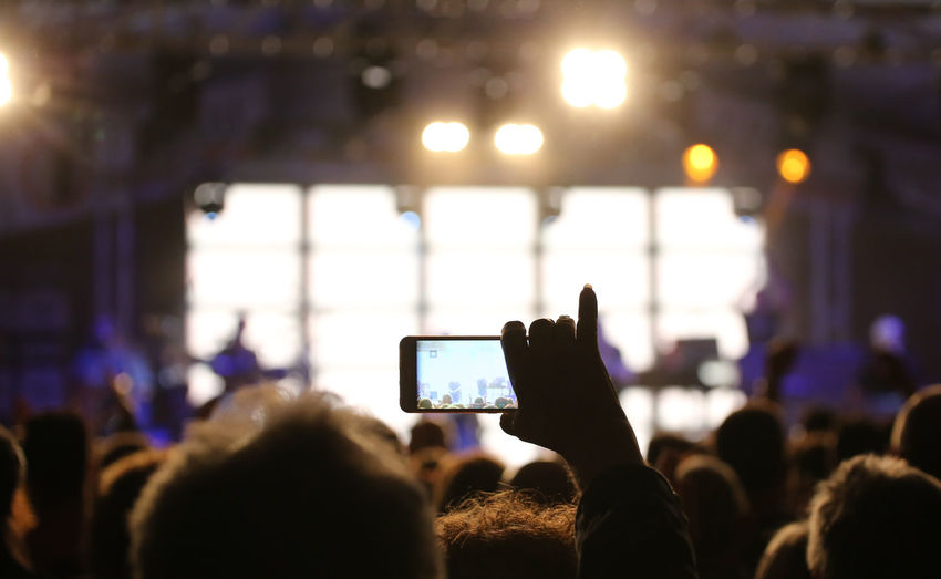 Person records a video of the live concert with the modern smartphone