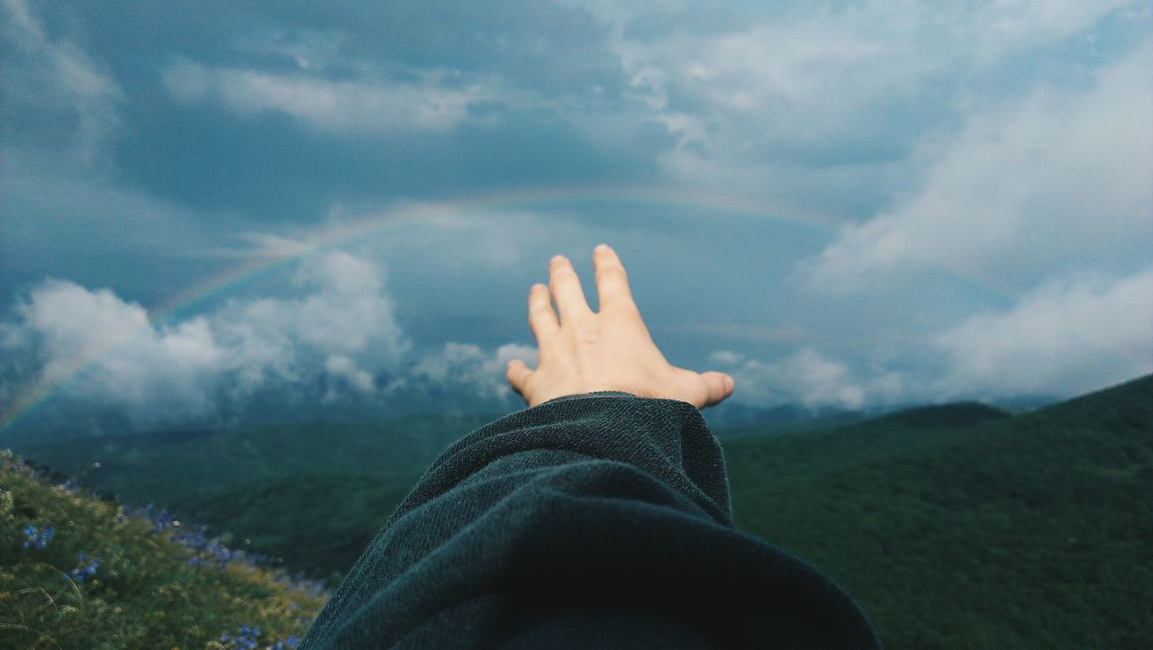 Close-up of hand pointing towards rainbow over countryside landscape