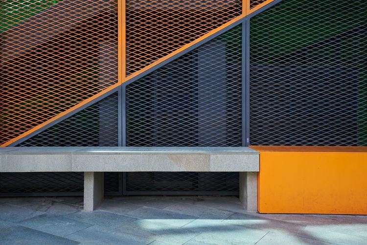 Metal fence against orange wall of building