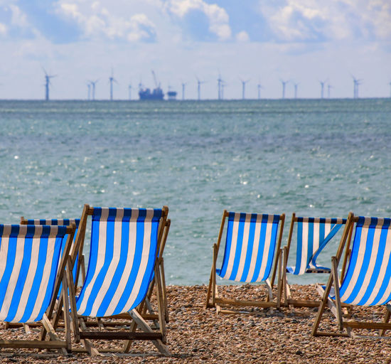 Deckchairs with off shore wind farm Absence Beach Beauty In Nature Chair Day Deck Chair Idyllic Land Nature No People Outdoor Chair Outdoors Sand Scenics - Nature Sea Seat Sky Tranquil Scene Tranquility Water