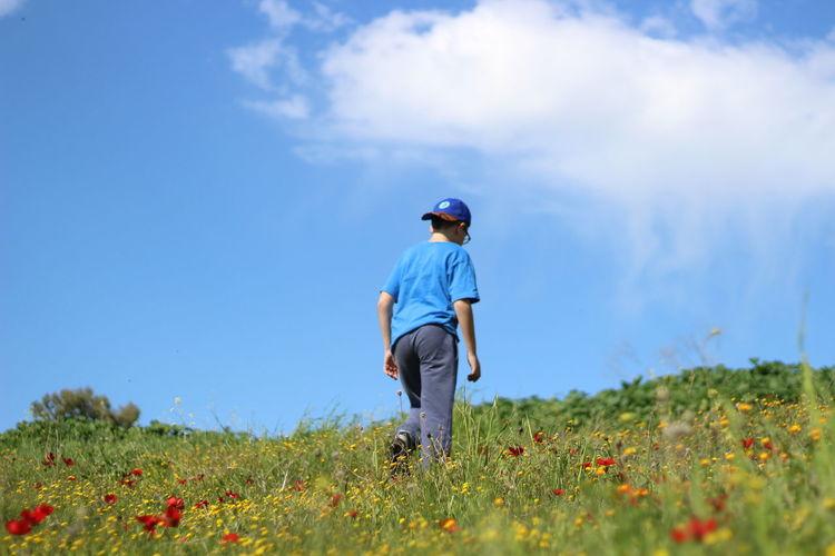 Rear View Of Boy Walking On Field Against Sky