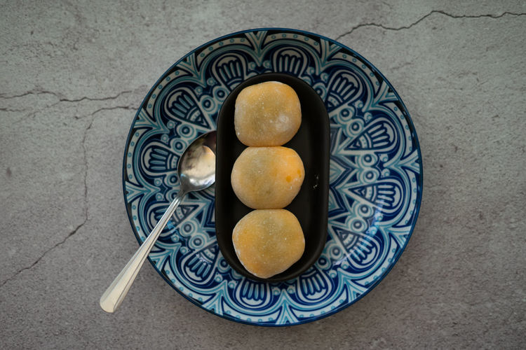 Yellow-colored japanese mochi in rice dough and on a pattern blue plate background.