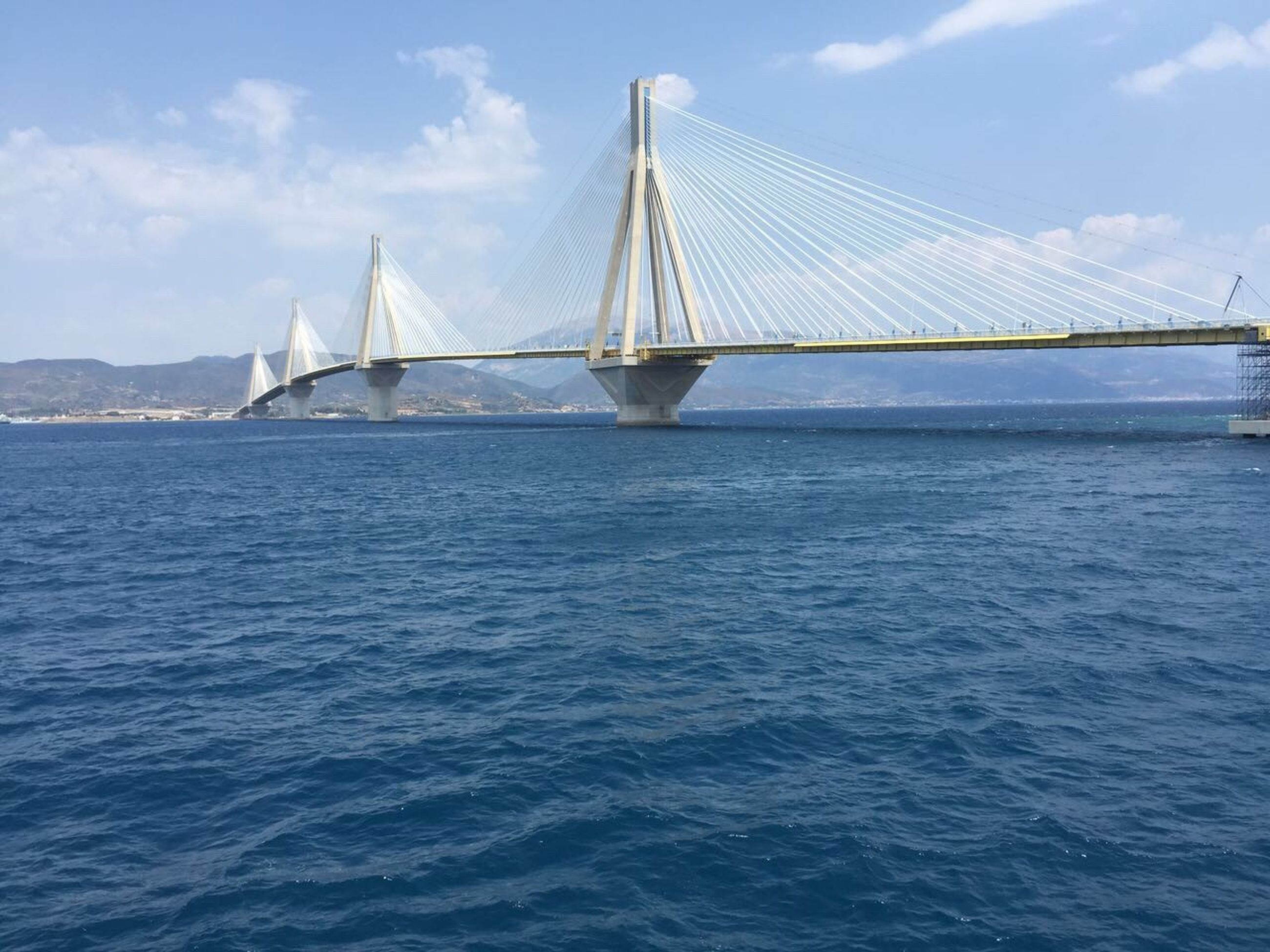 water, connection, sea, sky, built structure, architecture, bridge - man made structure, engineering, suspension bridge, cloud - sky, blue, bridge, rippled, travel destinations, cloud, tourism, day, nature, outdoors, ocean, tranquil scene, no people, tranquility, scenics, beauty in nature, cloudy