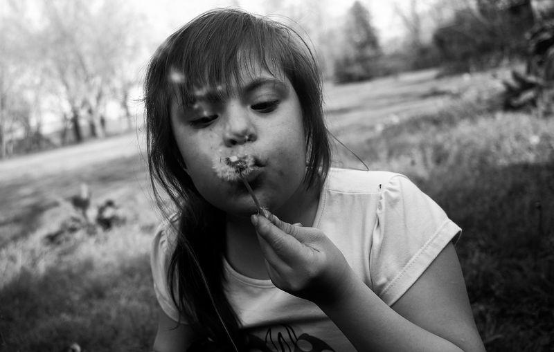 Teenage girl blowing dandelion on land
