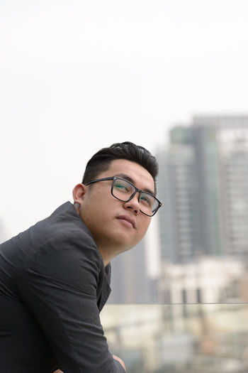 Young man looking away against cityscape