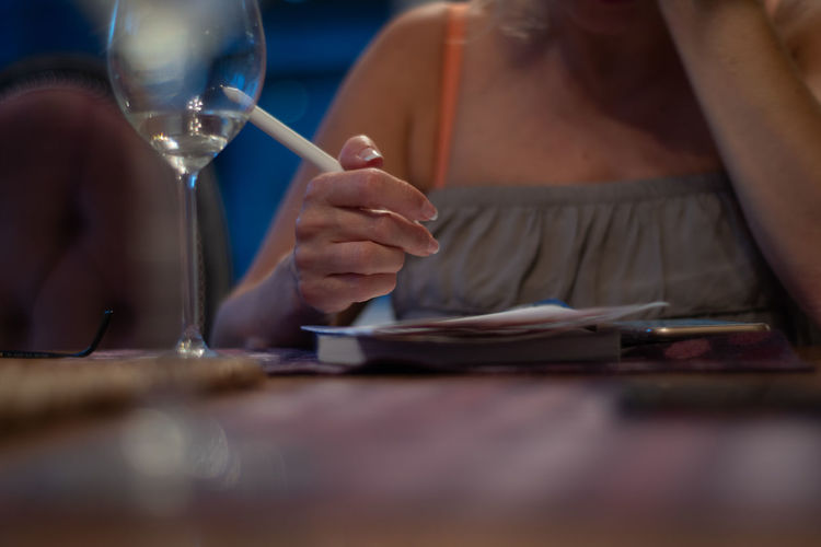 Midsection of woman holding glass while sitting on table