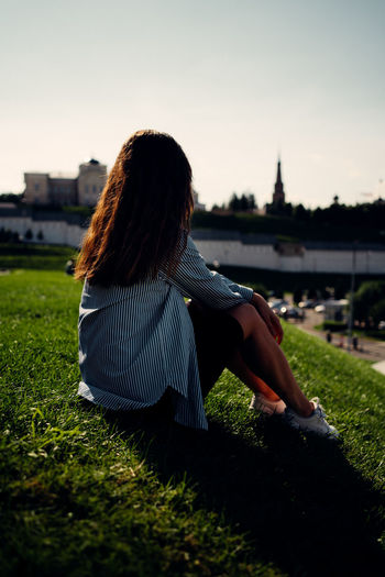 Rear view of woman sitting on grass against sky