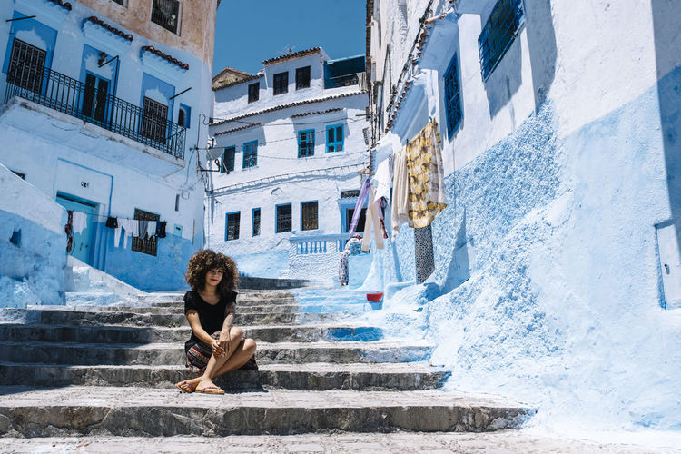 Portrait of woman sitting on staircase against buildings in city