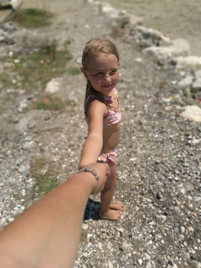 Cute Girl Holding Cropped Hand Of Mother At Beach
