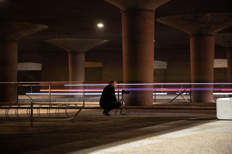 Rear view of woman sitting on bridge