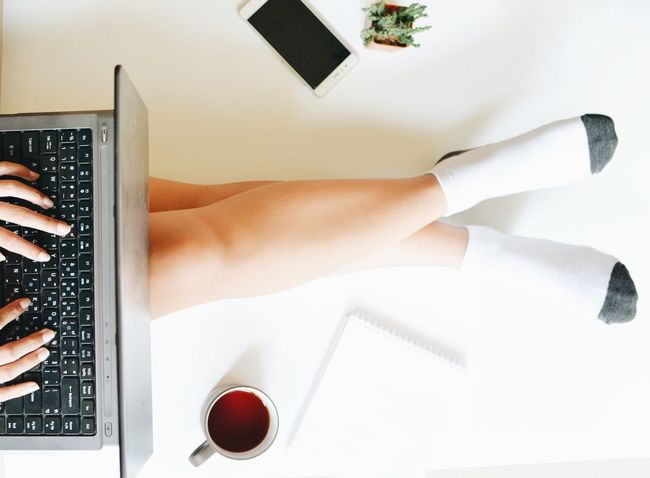 Top view beautiful woman legs with laptop,smart phone and coffee cup on white background Close-up Communication Computer Computer Keyboard Connection Directly Above Drink High Angle View Human Body Part Human Hand Indoors  Internet Keyboard Laptop One Person Photography Themes Portable Information Device Real People Table Technology Typing Using Laptop Wireless Technology Women Working