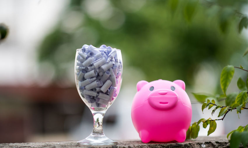 Close-up of piggy bank and wineglass on table