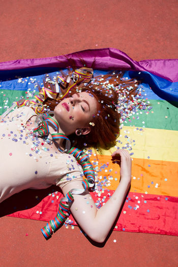 High Angle View Of Young Woman Lying With Confetti On Rainbow Flag