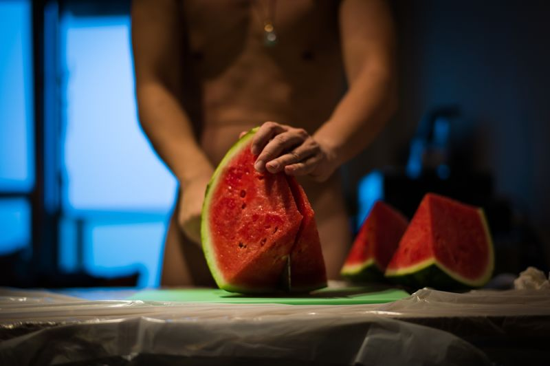 Midsection of naked man cutting watermelon
