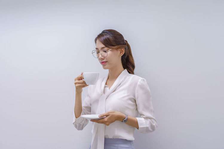 Young woman holding coffee while standing against white background
