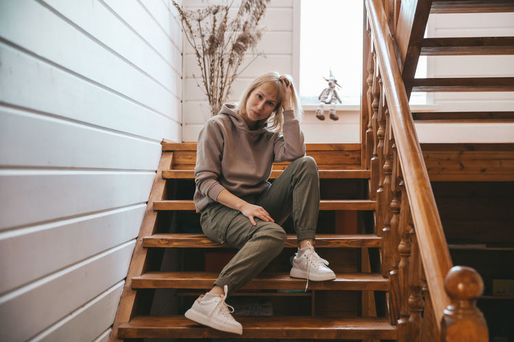 Full length of young woman sitting on staircase