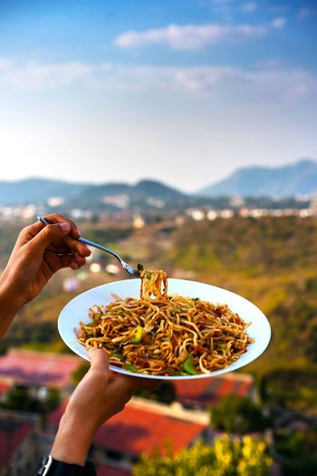 Cropped hand of person holding noodles with chopsticks against mountains