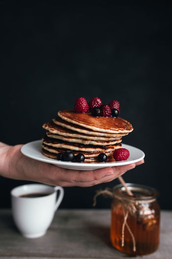 Juicy pancakes with berries and honey on white plate on human hand, jar and spoon, wooden table