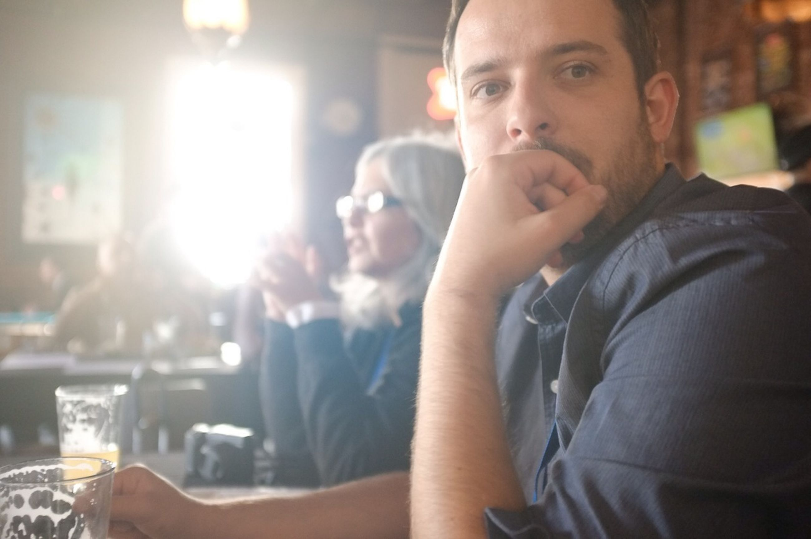 lifestyles, person, leisure activity, young adult, focus on foreground, casual clothing, front view, looking at camera, headshot, portrait, young men, waist up, holding, smiling, sitting, three quarter length