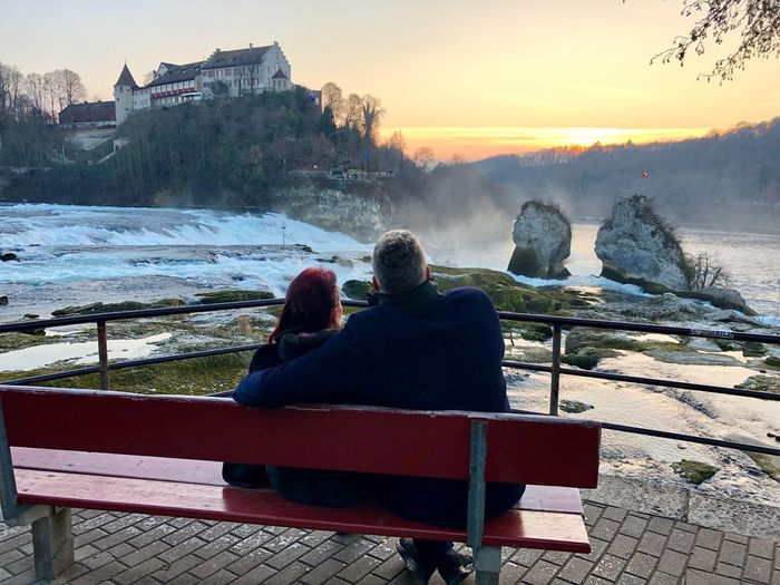 Rear view of people sitting on bench in winter
