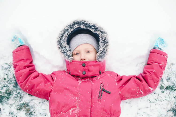 Directly above portrait of girl making snow angel on land