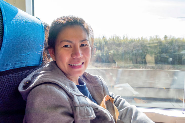 Portrait of smiling woman sitting in train by window