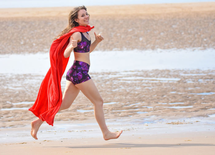 Full length of young woman wearing cape while running at beach