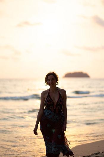 Woman walking on beach during sunset