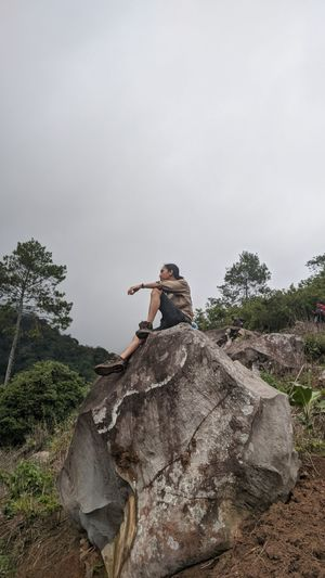 Young man on rock by land against sky