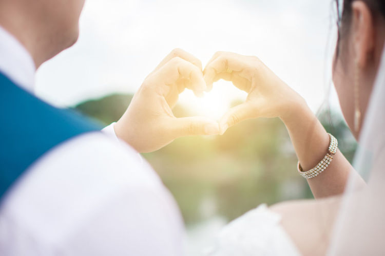 Cropped image of couple making heart shape with hands