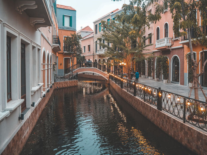 Canal by building in city
