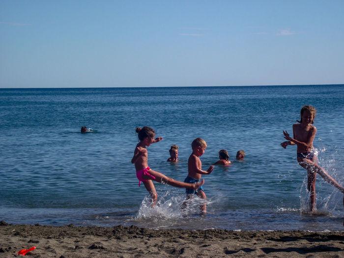 Children At Beach Against Sky