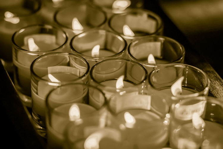Close-up of illuminated candles at temple